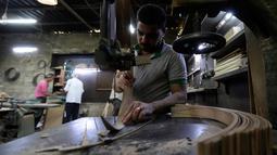 Pekerja memotong kayu untuk pembuatan alat musik Oud di sebuah rumah produksi di Damaskus, Suriah (17/7). Oud sering juga disebut Gitar Gambus yang bentuknya sepeti buah pir. (AFP Photo/Louai Beshara)