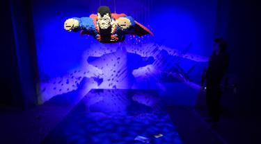 Seorang wanita berdiri dekat karakter pahlawan super dari DC yang dibuat dari Lego pada pameran Art of the Brick di La Vilette, Paris, Kamis (26/4). Tokoh superhero yang dibuat dengan Lego ini hasil karya seniman AS, Nathan Sawaya (AFP/Lionel BONAVENTURE)