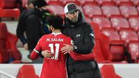 Manajer Liverpool, Jurgen Klopp, memeluk pemainnya, Mohamed Salah, setelah The Reds kalah 0-2 dari Everton dalam laga derbi Merseyside di Anfield pada pekan ke-25 Premier League, Minggu (21/2/2021). (PAUL ELLIS / POOL / AFP)