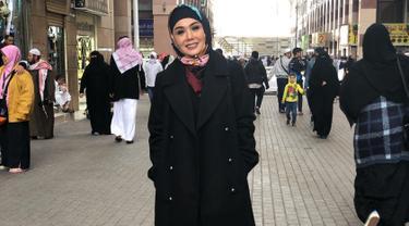 Yuni Shara tampak memesona mengenakan hijab bernuansa warna hitam dengan motif simpel. Coat berwarna hitam menambah kesan anggun dari dari ibu dua anak ini. Begini gaya Yuni saat menikmati indahnya kota Madina.(Liputan6.com/IG/@yunishara36)