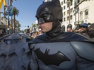"Pria berpakaian Batman berpose depan Batmobil terbaru dalam serial film "" Batman v Superman : Dawn of Justice "" di Los Angeles, California, (21/10/2015).  Acara Ini merupakan penghargaan terhadap pencipta Batman Bob Kane. (REUTERS/Mario Anzuoni)"