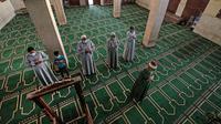 Imam memimpin Umat Muslim, yang mengenakan masker karena pandemi Covid-19, selama salat Idul Fitri di dalam sebuah masjid di desa Shamma, provinsi Nou delta, Menoufia di Mesir pada 24 Mei 2020. (Photo by Mohamed el-Shahed / AFP)