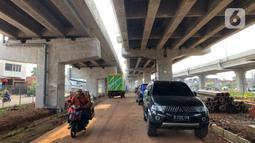 Pedagang melintasi mobil yang parkir di kolong jalan tol Becakayu di kawasan Cipinang Muara, Jakarta, Jumat (13/3/2020). Minimnya lahan parkir membuat sebagian orang tetap memarkirkan kendaraannya di kolong tol tersebut, meskipun telah terpampang larangan parkir. (Liputan6.com/Immanuel Antonius)
