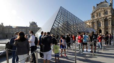 Pengunjung mengentre di piramida Louvre yang dirancang arsitek China Ieoh Ming Pei, pintu masuk ke Museum Louvre pada hari pertama pembukaan di Paris (6/7/2020). Setelah berbulan-bulan ditutup akibat lockdown Covid-19, Museum Louvre  kembali dibuka pada 6 Juli 2020. (AFP/Francois Guillot)