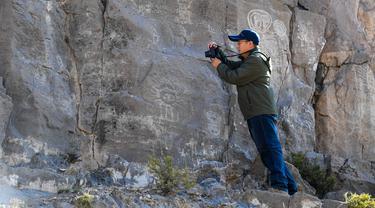 Seorang arkeolog memotret lukisan batu di klaster seni cadas Gunung Zhuozi di Daerah Otonom Mongolia Dalam, China pada 17 Oktober 2020. Gunung Zhuozi adalah tempat dengan banyak lukisan batu yang berguna untuk penelitian tentang asal muasal nomad kuno di China. (Xinhua/Peng Yuan)