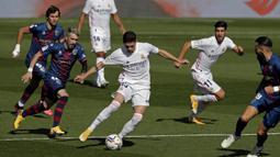 Gelandang Real Madrid, Federico Valverde, berusaha melewati pemain Huesca pada laga lanjutan Liga Spanyol di Stadion Alfredo Di Stefano, Sabtu (31/10/2020) malam WIB. Real Madrid menang 4-1 atas Huesca. (AP Photo/Manu Fernandez)