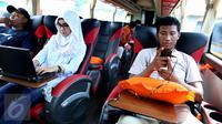Penumpang Bus Harapan Jaya menggunakan laptop dan charger handphone yang merupakan fasilitas bus di Pool Ciputat, Tangerang Selatan. Penumpang bisa menggunakan fasilitas seperti wi fi, charger listrik dan USB. (Liputan6.com/Fery Pradolo)