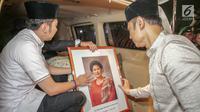 Agus Harimurti Yudhoyono dan Edhie Baskoro Yudhoyono membawa pigura foto almarhumah Ani Yudhoyono di Lanud Halim Perdanakusumah, Jakarta Timur, Sabtu (1/6/2019). Almarhumah meninggal dunia di National University Hospital (NUH) Singapura dan disemayakamkan di Puri Cikeas. (Liputan6.com/Faizal Fanani)