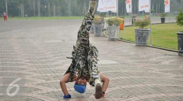 Kopral Bagyo, anggota Polisi Militer Angkatan Darat IV/Surakarta, melakukan aksi jungkir balik mengelilingi tugu Monas, Jakarta, Jumat (17/6). Aksi ini bagian dari kampanye bahaya narkoba dan perayaan ulang tahun ke-70 POM AD (Liputan6.com/Gempur M Surya)