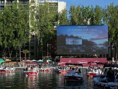 """Orang-orang di atas kapal menghadiri Cinema on the Water, yang diselenggarakan Paris Plages selama pemutaran """"Le Grand Bain"""" di Paris, Prancis pada 18 Juli 2020. Paris menghadirkan terobosan baru dengan bioskop terapung lengkap dengan perahu yang tetap menjaga jarak. (AP Photo/Rafael Yaghobzadeh)"""