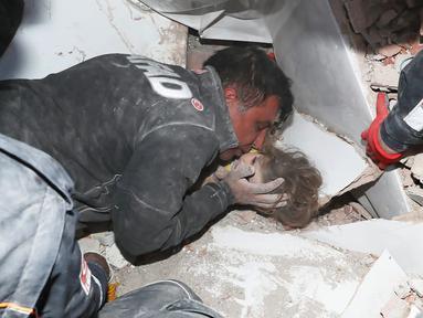 Petugas penyelamat memegang Ayda Gezgin, 3, yang terjebak reruntuhan gedung apartemen setelah gempa bumi dahsyat di kota Izmir, Turki, Selasa (3/11/2020). Ayda Gazgin berhasil diselamatkan dari bawah reruntuhan bangunan setelah terkubur selama 4 hari atau sekitar 91 jam. (AFAD via AP)