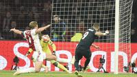 Striker Real Madrid, Karim Benzema, melepaskan tembakan yang bersarang di gawang Ajax pada leg pertama 16 besar Liga Champions, di Johan Cruijff ArenA, Amsterdam, Rabu (13/2/2019). (AFP/John Thys)