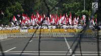 Massa aksi tertahan di belakang dua barikade yang dipasang pihak keamanan di Jalan Medan Merdeka Barat, Jakarta, Kamis (27/6/2019). Massa aksi berkumpul terkait pelaksanaan sidang putusan perselisihan hasil Pilpres 2019 di Gedung Mahkamah Konstitusi. (Liputan6.com/Helmi Fithriansyah)