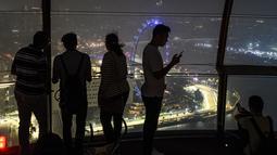Turis melihat Sirkuit Marina Bay Street yang diselimuti kabut asap di Singapura (18/9/2019). Kabut asap dari kebakaran hutan yang terjadi di Sumatra dan Kalimantan membuat kelangsungan GP Singapura 2019 diliputi ketidakpastian. (AFP Photo/Mladen Antonov)
