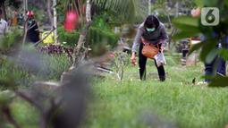 Peziarah menabur kembang di salah satu makam di Tempat Pemakaman Umum Karet Bivak, Jakarta, Sabtu (18/4/2020). Selama masa PSBB, peziarah yang memasuki kawasan TPU dibatasi dan diwajibkan menggunakan masker sebagai langkah pencegahan penyebaran virus Covid-19. (Liputan6.com/Helmi Fithriansyah)