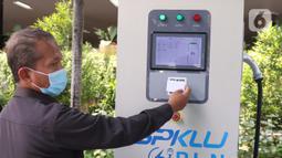 Petugas mengetap kartu sebelum mengisi daya listrik di SPKLU di Kantor PLN Pusat, Jakarta, Senin (9/11/2020). Pemerintah mendorong peningkatan ketersediaan  SPKLU hingga 2025 ditargetkan terbangun 3.465 unit SPKLU dan lima tahun kemudian menjadi 7.146 unit SPKLU. (Liputan6.com/Angga Yuniar)