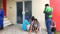 Nia, ibu EN tertunduk sedih di depan ruang Instalasi Forensik RS Bhayangkara Palembang (Liputan6.com / Nefri Inge)