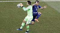 Kiper Polandia Lukasz Fabianski menangkap bola dengan striker Jepang Yoshinori Muto berusaha mengejar pada partai Grup H Piala Dunia 2018 di Volgograd Arena, Kamis (28/6/2018). (AP Photo/Themba Hadebe)