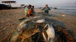 Nelayan Palestina mengenakan masker saat mereka menangkap kepiting di pantai laut Mediterania di Beit Lahyia, Jalur Gaza utara pada 21 September 2020. (AP Photo / Hatem Moussa)