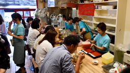 Pelanggan menikmati kakigori atau es serut di distrik Yanaka Tokyo, Jepang (21/6/2019). makanan penutup musim panas yang menyegarkan ini terbuat dari campuran es serut, sirup buah dan susu kental manis. (AFP Photo/Toshifumi Kitamura)