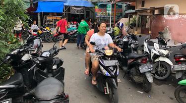 Sejumlah sepeda motor terparkir di sekitar Jalan Kebon Pala II, Jakarta, Selasa (25/2/2020). Banjir yang merendam kawasan tersebut menyebabkan warga mengungsikan kendaraannya ke tempat yang lebih tinggi. (Liputan6.com/Immanuel Antonius)