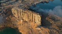Dalam gambar drone ini, silo yang hancur berada di antara puing-puing setelah ledakan di pelabuhan Beirut, Lebanon, Rabu (5/8/2020). Ledakan di kawasan pelabuhan itu mengguncangkan seluruh ibu kota, mengguncang bangunan, dan menebarkan kepanikan di antara warganya. (AP Photo/Hussein Malla)