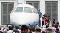 Pengunjung antre untuk masuk ke Pesawat N250 pada Habibie Festival di Museum Nasional, Jakarta, Minggu (14/8). Tingginya antusiasme warga membuat pengunjung harus antre untuk dapat melihat bagian dalam kendaraan tersebut. (Liputan6.com/Immanuel Antonius)