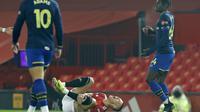 Gelandang Manchester United, Scott McTominay mengerang kesakitan usai menerima tekel horor dari pemain Southampton, Alexandre Jankewitz (paling kanan), Rabu (03/02/2021) dini hari WIB. (PHIL NOBLE / POOL / AFP)