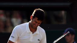 Petenis Serbia, Novak Djokovic meringis kesakitan saat melawan Tomas Berdych (Ceko) pada perempatfinal Wimbledon 2017, Rabu (12/7). Melawan Berdych cedera Djokovic kambuh, ia  terlihat mengalami masalah dengan cedera lengannya. (Gareth Fuller/PA via AP)
