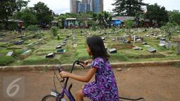 Seorang anak bermain sepeda di sekitar TPU Karet Bivak, Jakarta, Jumat (13/1). Semakin berkurangnya lahan hijau menyebabkan anak-anak di Ibukota terpaksa bermain di tempat yang tidak semestinya. (Liputan6.com/Immanuel Antonius)