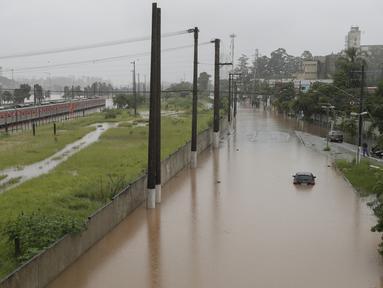 Sebuah kereta metropolitan terlihat di jalur rel yang banjir yang membentang di sepanjang sungai Pinheiros di Sao Paulo, Brasil, Senin, (10/2/2020). Hujan deras yang membanjiri kota, menyebabkan pinggir sungai utama meluap. (AP Photo/Andre Penner)