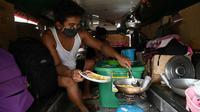 Daniel Flores memasak makan siang di dalam jeepney mereka yang berfungsi sebagai rumah sementara di Manila, 12 Agustus 2020. Angkutan ikonik di Filipina itu belum dapat mengangkut penumpang sejak Maret akibat lockdown Covid-19 yang membuat jutaan orang kehilangan pekerjaan. (Ted ALJIBE/AFP)