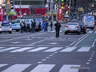 Petugas polisi terlihat sedang melakukan pemeriksaan di lokasi penembakan di Times Square di New York, AS (8/5/2021). Menurut laporan, tiga orang, termasuk seorang balita terluka dalam penembakan itu. (AFP/Kena Betancur)