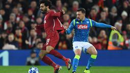 Gelandang Liverpool, Mohamed Salah, berusaha melewati bek Napoli, Mario Rui, pada laga Liga Champions di Stadion Anfield, Liverpool, Selasa (11/12). Liverpool menang 1-0 atas Napoli. (AFP/Paul Ellis)