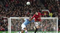 Penyerang Manchester City, Raheem Sterling berebut bola udara dengan bek Manchester United, Victor Lindelof pada pertandingan leg pertama semifinal Piala Liga Inggris di Old Trafford (7/1/2020). City menang 3-1 atas MU. (AP Photo / Jon Super)