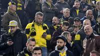Suporter mencari informasi terkait ledakan bus tim Dortmund di Signal Iduna Park, Dortmund, (11/4/2017). Laga perempatfinal Liga Champions akhirnya ditunda akibat ledakan pada bus tim Die Borussen.(AP/ Federico Gambarini/dpa via AP)