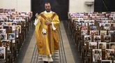 Pastor Katolik Georges Nicoli merayakan misa Kamis Putih disiarkan langsung di Facebook, dengan foto-foto jemaat yang ditempel dibangku di gereja Notre Dame De Lourdes di Bastia, di pulau Korsika Mediterania, Prancis (9/4/2020). (AFP/Pascal Pochard-Casabianca)