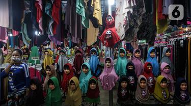 Seorang perempuan melintas di depan penjual gamis dan baju anak di pasar Parung, Bogor, Jawa Barat, Kamis (18/2/2021). Dampak pandemi COVID-19 yang berkepanjangan pedagang mengaku omset penjualan gamis dan baju anak turun 85 persen semenjak awal tahun lalu hingga sekarang. (Liputan6.com/Johan Tallo)