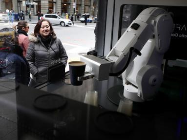 Pelanggan menyaksikan robot barista membuat kopi di Cafe X, San Francisco, California, AS, Selasa (12/2). Cafe X menggunakan robot untuk menyajikan makanan dan minuman. (Justin Sullivan/Getty Images/AFP)