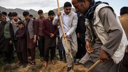 Teman dan kerabat memakamkan jenazah kepala fotografer AFP Afghanistan Shah Marai Faizi di Gul Dara, Kabul (30/4). Shah Marai merupakan korban ledakan di ibu kota Afghanistan, Kabul yang terjadi pada hari Senin (30/4). (Andrew Quilty / POOL / AFP)