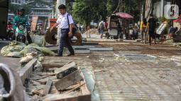 Pejalan kaki melintasi trotoar yang sedang direvitalisasi di kawasan Kramat Raya, Jakarta, Rabu (6/11/2019). Revitalisasi trotoar menyebabkan para pejalan kaki harus berjalan di pinggir jalan dan bersinggungan dengan sepeda motor. (Liputan6.com/Faizal Fanani)