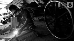 Penyandang disabilitas Catur Bambang (45) menyelesaikan pembuatan sepeda motor roda tiga di bengkelnya, Jalan Wijaya Kusuma, Ciputat Timur, Tangerang Selatan, Banten, Selasa (5/11/2019). Sepeda motor roda tiga diharapkan membantu penyandang disabilitas bermobilisasi. (merdeka.com/Arie Basuki)