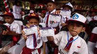 Sejumlah siswa memperlihatkan Kartu Indonesia Pintar (KIP) di Ambon, Maluku, (8/2). Jokowi membagikan sekitar 1.265 KIP untuk para siswa di Ambon. (Liputan6.com/Faizal Fanani)