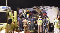 Petugas memeriksa bangkai bus yang kecelakaan akibat menabrak sebuah truk di jalan raya antara Ibri dan Fahud, Oman bagian barat, Selasa (1/3). Sebanyak 18 orang dari beberapa kewarganegaraan tewas dan 14 lainnya luka-luka. (STRINGER/Omani Police/AFP)