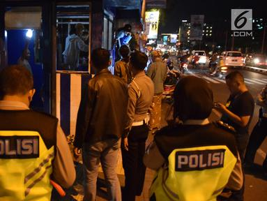 Polisi berjaga di pos polisi yang sedang diperbaiki usai dibakar massa saat peringatan Hari Buruh di Yogyakarta, Selasa (1/5) malam. Pos polisi ini terletak di pertigaan UIN Sunan Kalijaga Yogyakarta. (Liputan6.com/Gholib)