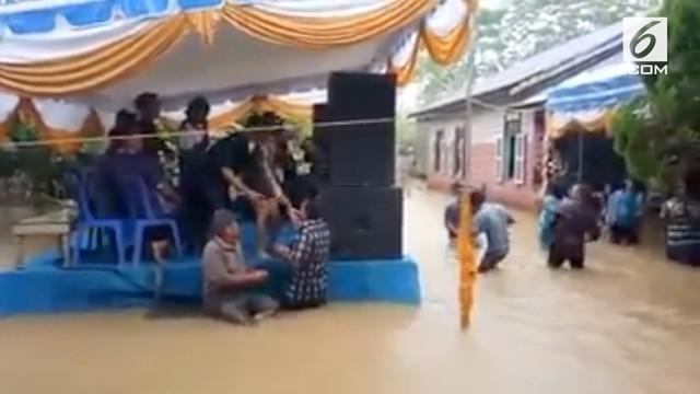 Sebuah resepsi pernikahan tetap digelar meskipun sedang dilanda banjir. Meski air yang menggenangi lokasi resepsi setinggi pinggang orang dewasa, tak menyuruti para undangan untuk hadir.