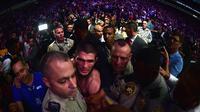 Khabib Nurmagomedov tengah diamankan oleh petugas keamanan menuju kamar ganti usai bertarung melawan Conor McGregor (Harry How/AFP)