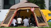 Foto 11 September 2018, karyawan perusahaan bekerja di dalam tenda kemah di halaman luar gedung kantor di Tokyo. Beberapa kantor di Jepang membebaskan pegawainya untuk bekerja di mana saja, mulai dari tenda hingga tempat karaoke. (Toshifumi KITAMURA/AFP)