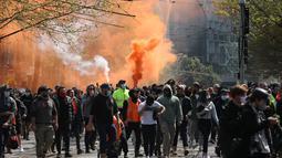 Suar dinyalakan ketika pekerja konstruksi dan demonstran menghadiri protes terhadap peraturan Covid-19 di Melbourne (21/9/2021). Polisi telah menangkap setidaknya 44 orang setelah adegan liar, di mana beberapa petugas diduga terluka. (AFP/Con Chronis)