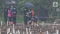 Keluarga dan kerabat jenazah kasus COVID-19 mengunjungi pemakaman di TPU Bambu Apus, Jakarta Timur, Selasa (16/2/2021). Pemangkasan petak makam di TPU Bambu Apus tersebut dilakukan agar bisa menampung lebih banyak jenazah, mengingat lahan pemakaman terbatas. (Liputan6.com/Herman Zakharia)